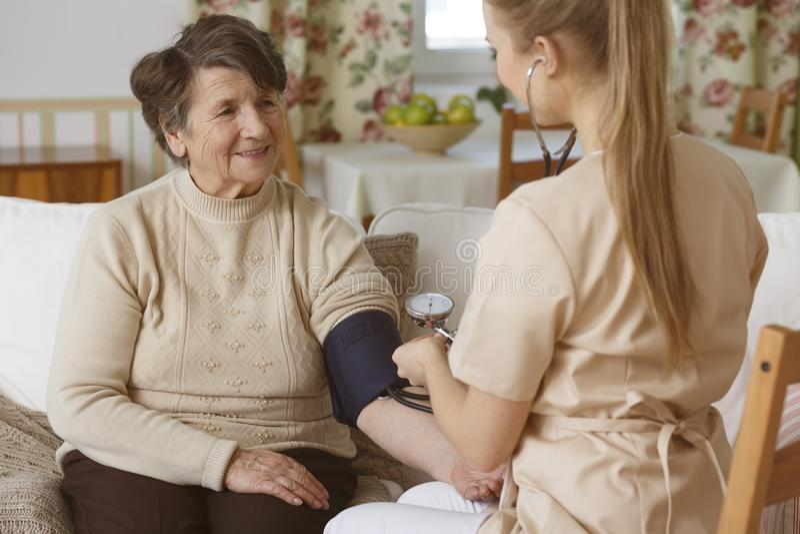 Nurse checking blood pressure stock photo