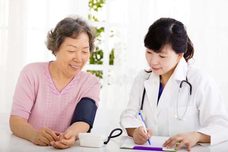 Nurse checking senior woman blood pressure stock images