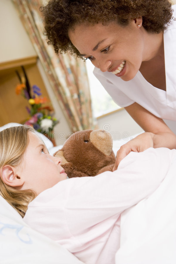 Nurse Checking Up On Young Girl In Hospital stock photography