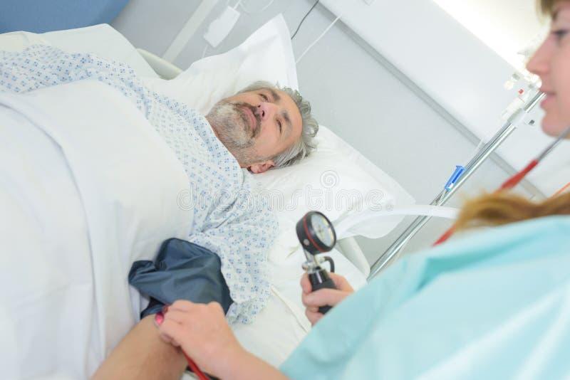Nurse checkking male patients pressure stock photos