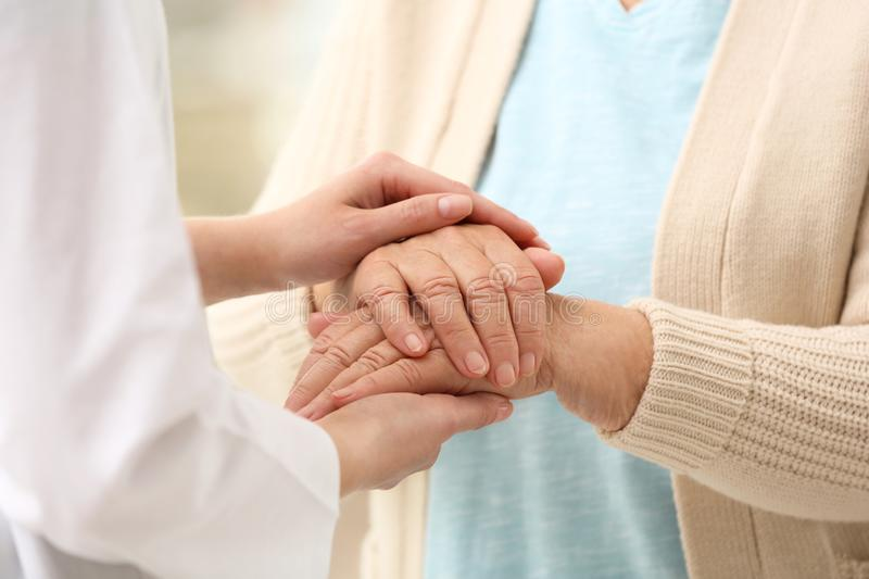 Nurse comforting elderly woman against blurred background. Assisting senior generation stock image