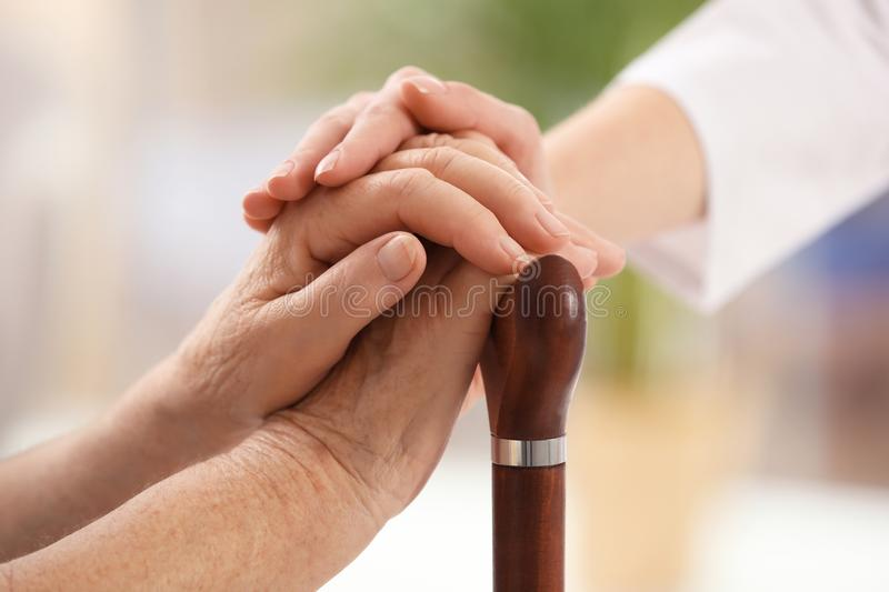 Nurse comforting elderly woman with cane against blurred background. Assisting senior generation royalty free stock photography