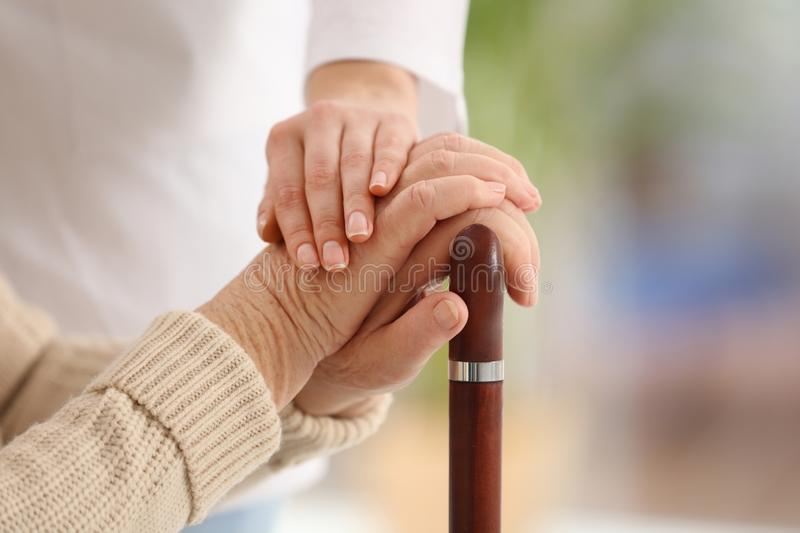Nurse comforting elderly woman with cane against blurred background. Assisting senior generation stock photos