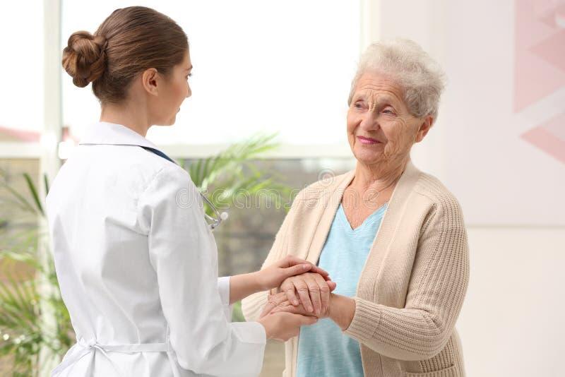Nurse comforting elderly woman. Assisting senior generation stock images