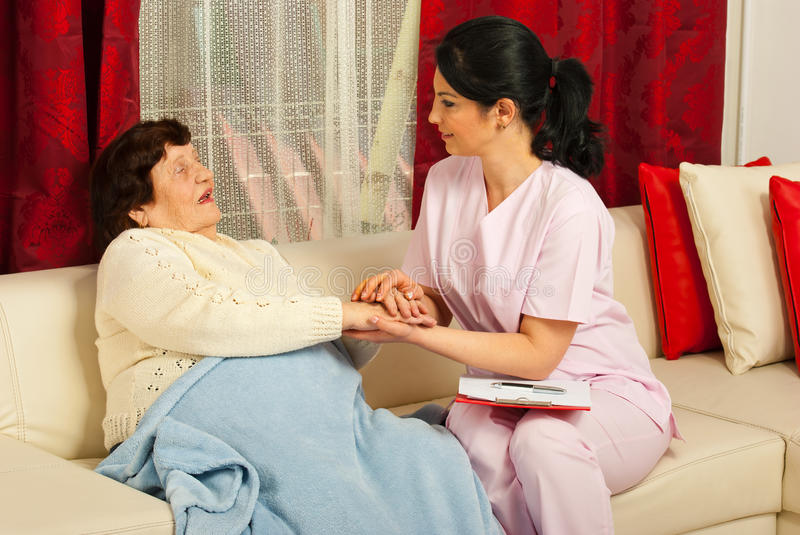 Nurse comforting sick elderly woman. Nurse comforting sick elderly women in her home stock photography