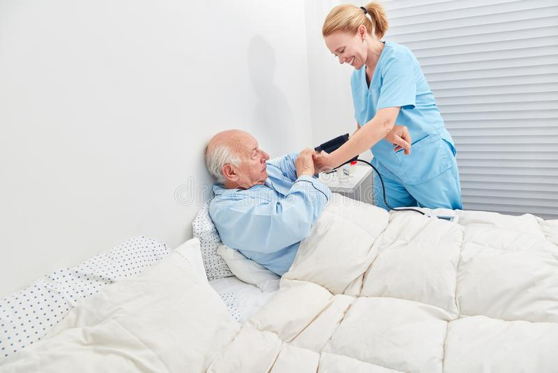 Nurse controls blood pressure of senior royalty free stock photo
