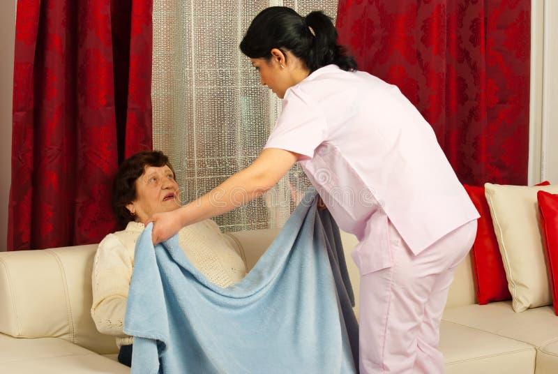 Nurse covering elderly with blanket