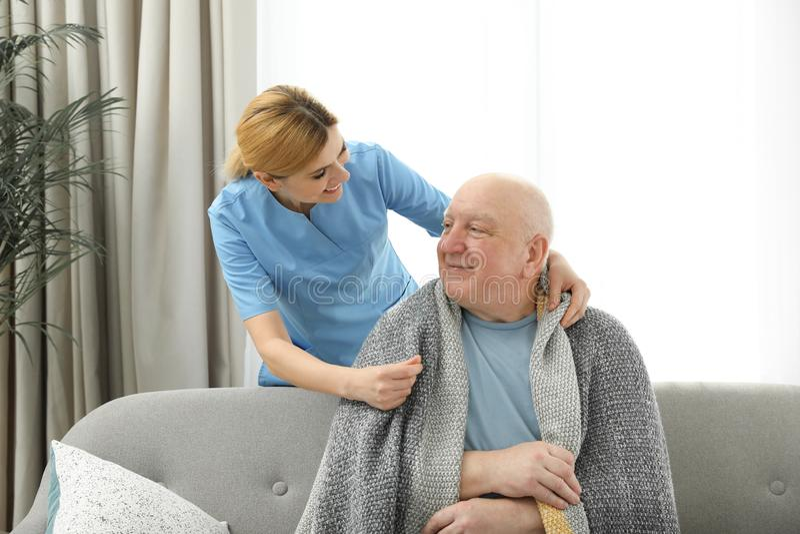 Nurse covering elderly man with blanket. Assisting senior people stock photo