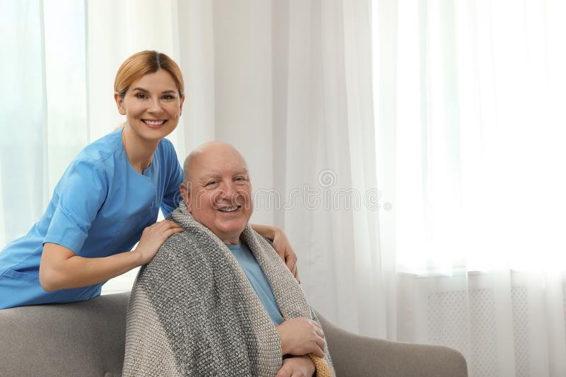 Nurse covering elderly man with blanket indoors. Assisting senior people royalty free stock image