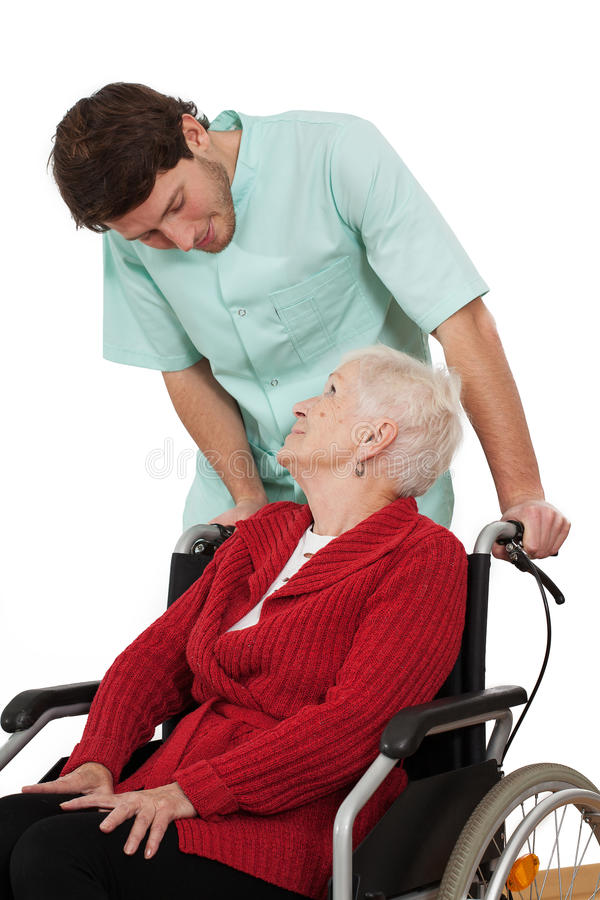 Nurse with disabled. Nurse keeping company to elder disabled women on wheelchair royalty free stock image