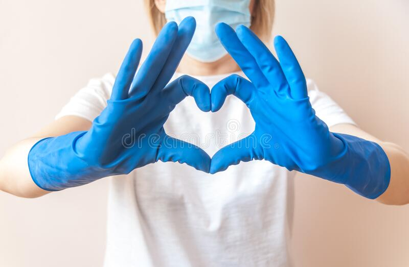 Nurse doctor hands in blue medical gloves in the shape of heart against the background of her body. Close up. Blurred background. Thanks to health workers stock images