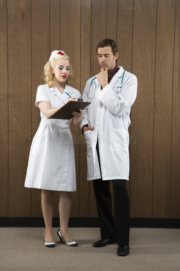 Nurse and doctor looking at clipboard. Mid-adult Caucasian female nurse and male doctor standing looking at clipboard stock images