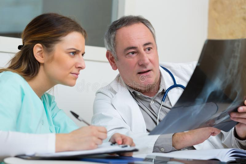 Nurse and doctor looking at x-ray. Nurse royalty free stock photo
