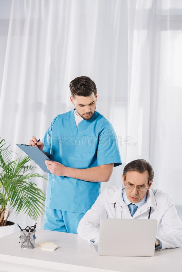 Nurse and doctor looking. At working laptop stock images