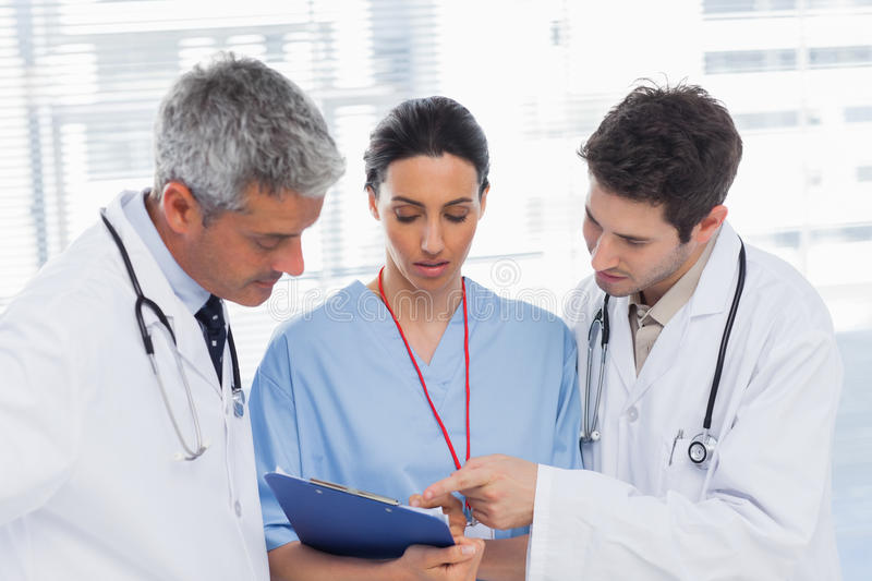 Nurse and doctors looking together a file. In medical office stock image