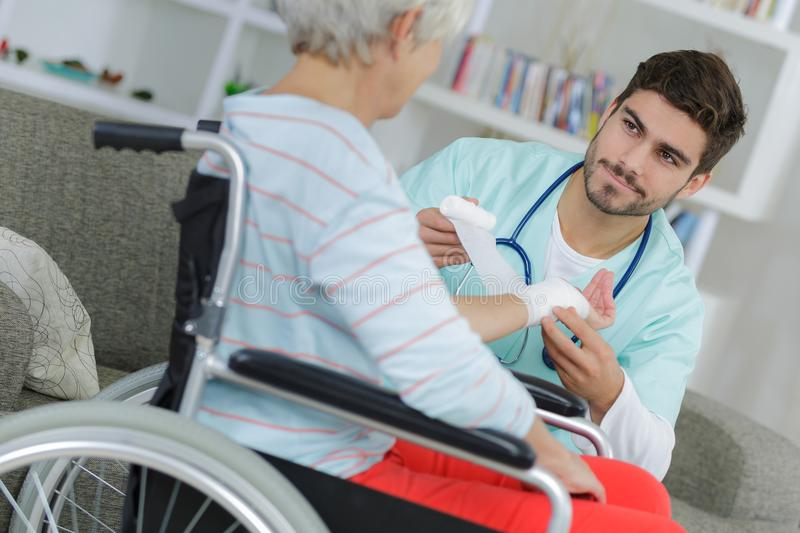 Nurse doing bandages on old lady on wheelchair. Nurse doing bandages on an old lady on wheelchair royalty free stock images