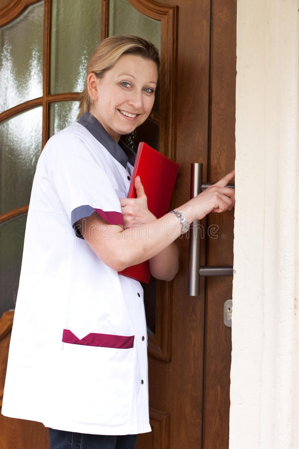 Nurse at the door for home visit. Geriatric nurse makes a house call and rings the door stock photo