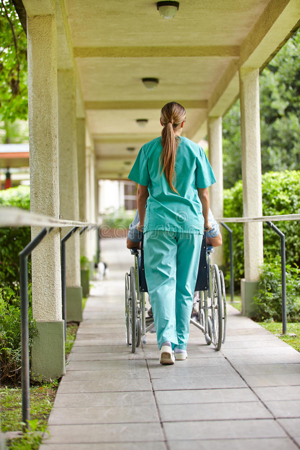 Download Nurse driving wheelchair stock photo. Image of nature - 29195382
