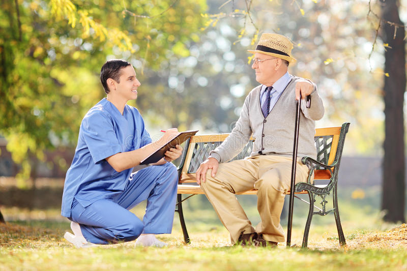 Nurse and an elderly having conversation in park stock images