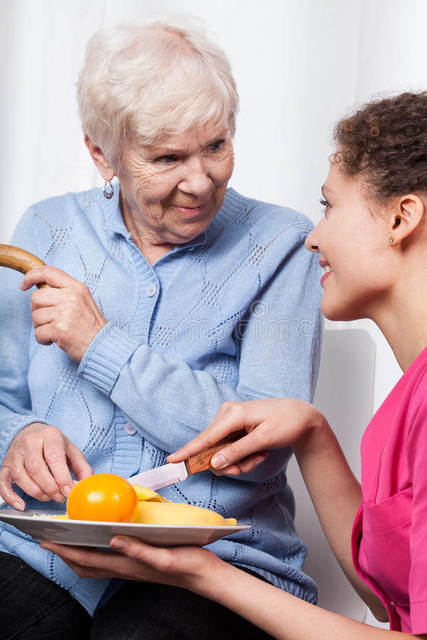 Nurse and elderly woman eating fruits stock photos