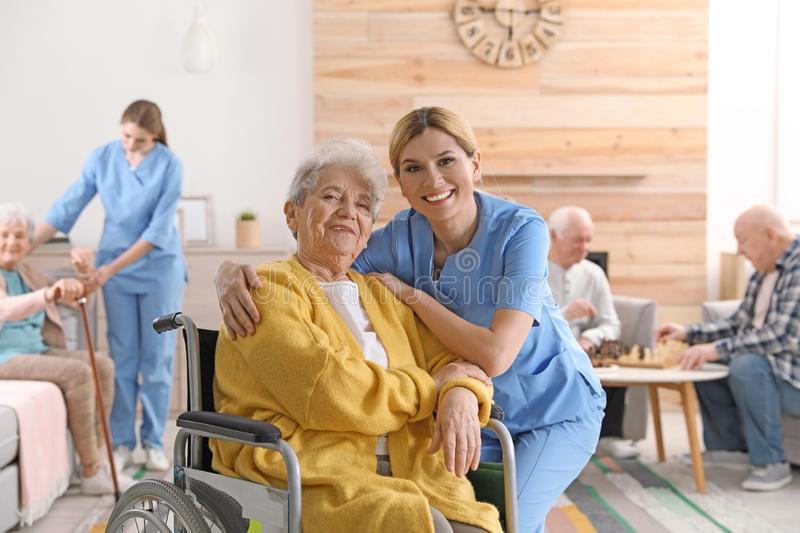 Nurse with elderly woman in wheelchair at retirement home royalty free stock image