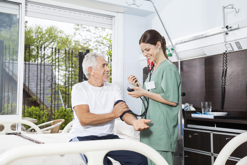 Nurse Examining Blood Pressure Of Senior Man In Rehab Center. Happy female nurse examining blood pressure of senior men in rehab center royalty free stock photo