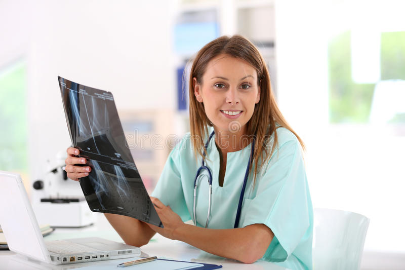 Nurse examining x-ray results. Nurse reading X-Ray results in hospital office royalty free stock image