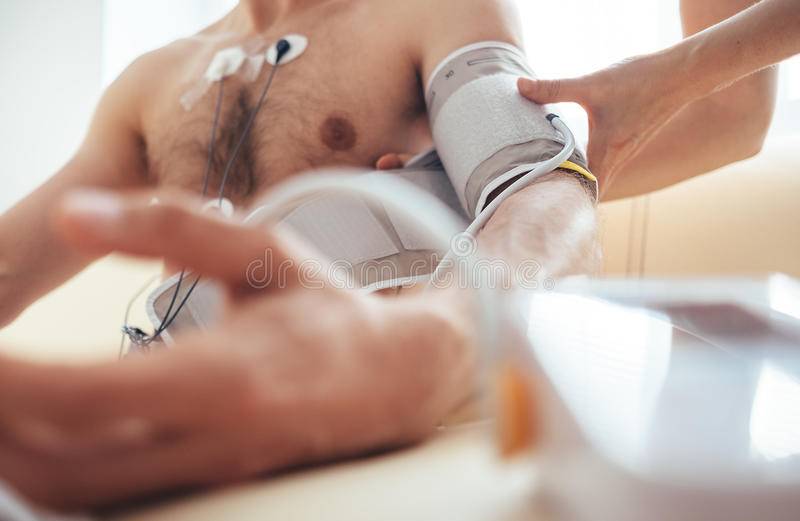 A nurse fastens the tonometer cuffs on the patient`s arm stock images