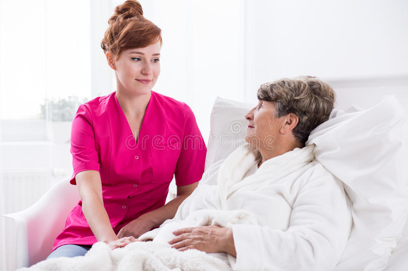 Nurse and geriatric ward patient. Image of young nurse and geriatric ward female patient royalty free stock images