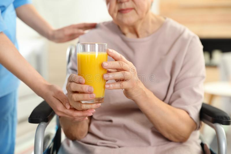 Nurse giving glass of juice to elderly woman indoors. Assisting senior people royalty free stock photo