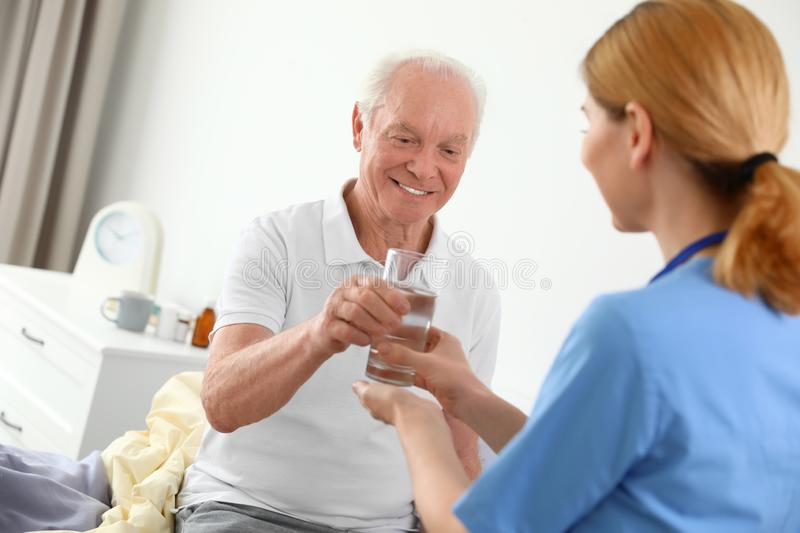 Nurse giving glass of water to elderly man. Medical assistance royalty free stock photo