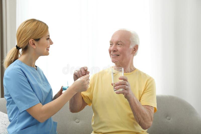 Nurse giving medication to elderly man indoors stock photography