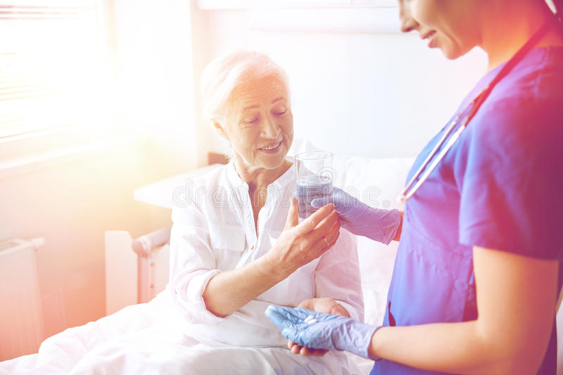 Nurse giving medicine to senior woman at hospital. Medicine, age, health care and people concept - nurse giving medication and glass of water to senior women at royalty free stock images