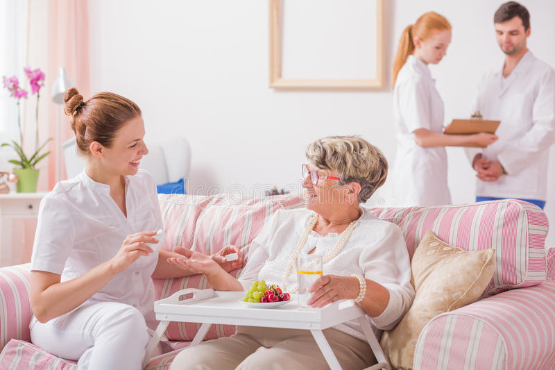Nurse giving medicines in private clinic. Elderly lady sitting on a couch with a tray and a young nurse giving her medicines in private clinic stock images