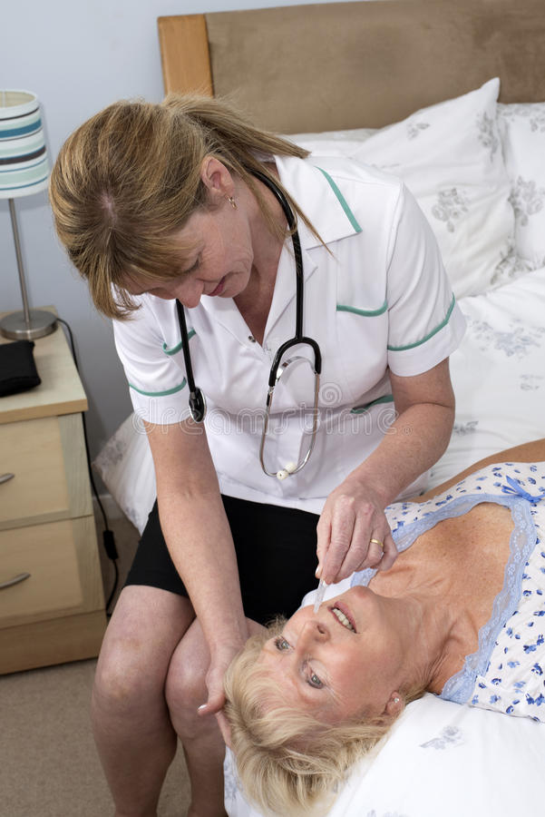 Nurse giving nose drops to patient royalty free stock images