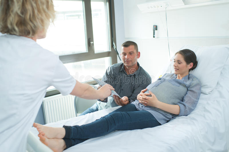 Nurse giving paper to pregant woman and husband royalty free stock photos