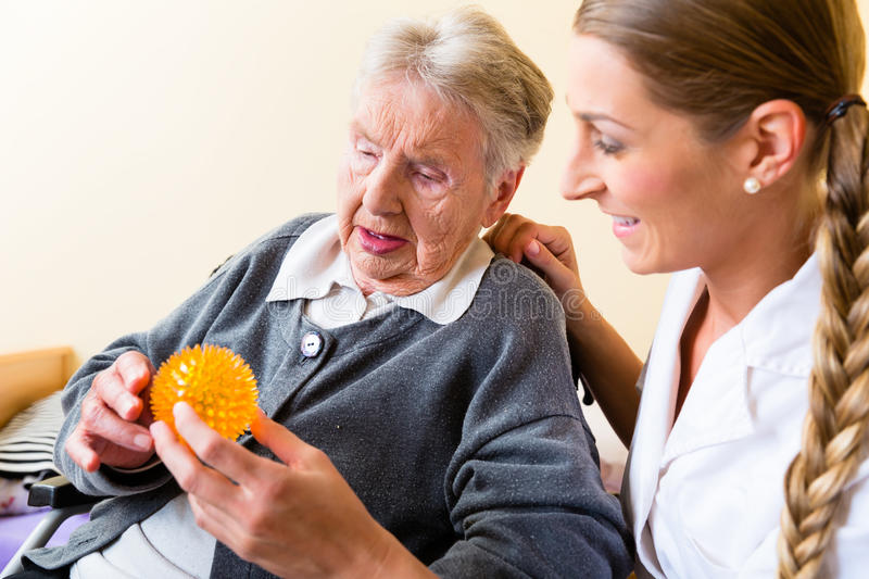 Nurse giving physical therapy to senior woman stock images