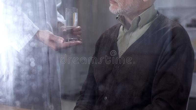 Nurse giving pill and water glass to senior male patient, hospital care, illness stock images