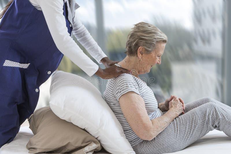 Nurse giving shoulder and neck massage to woman at home. Nurse giving leg massage to woman at home stock images
