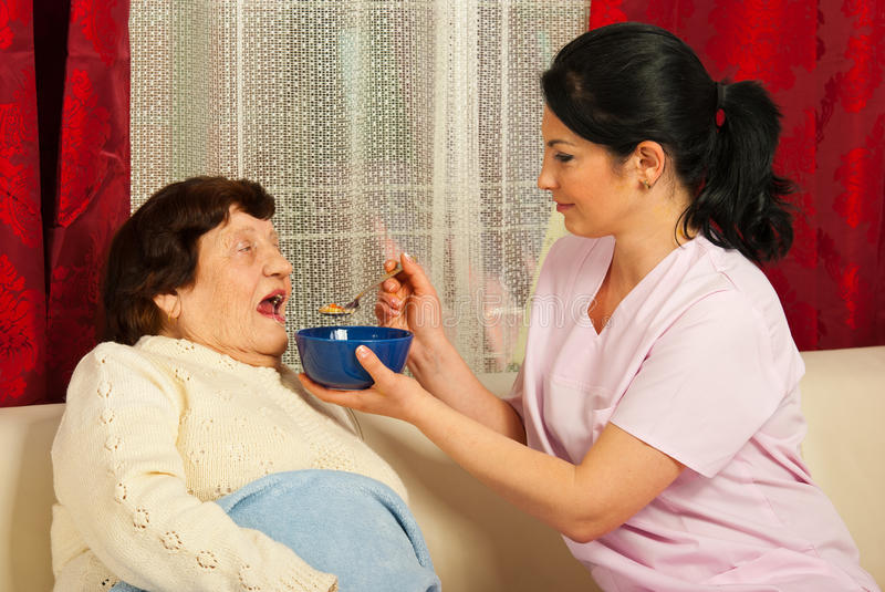 Nurse giving soup to elderly woman. Nurse giving soup to sick elderly women at home stock images