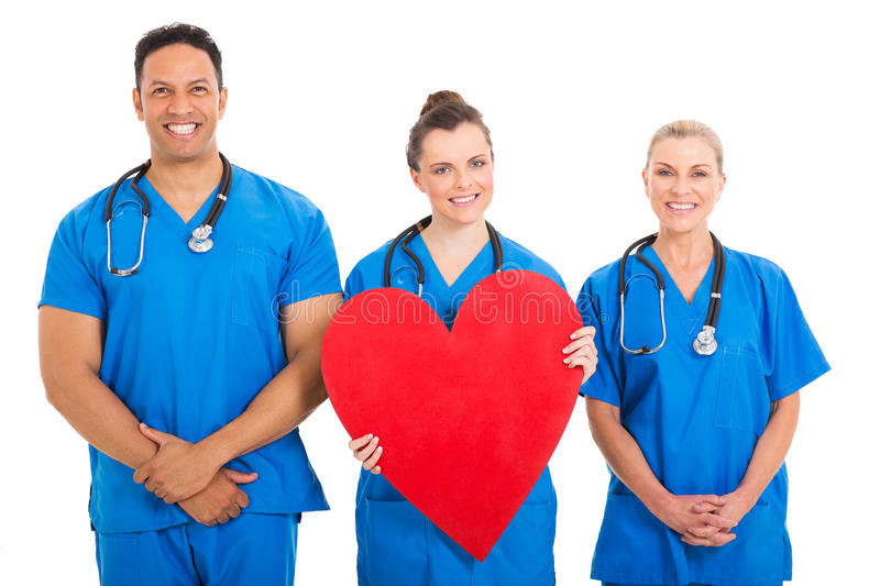 Nurse heart shape. Beautiful young nurse holding heart shape with colleagues royalty free stock images