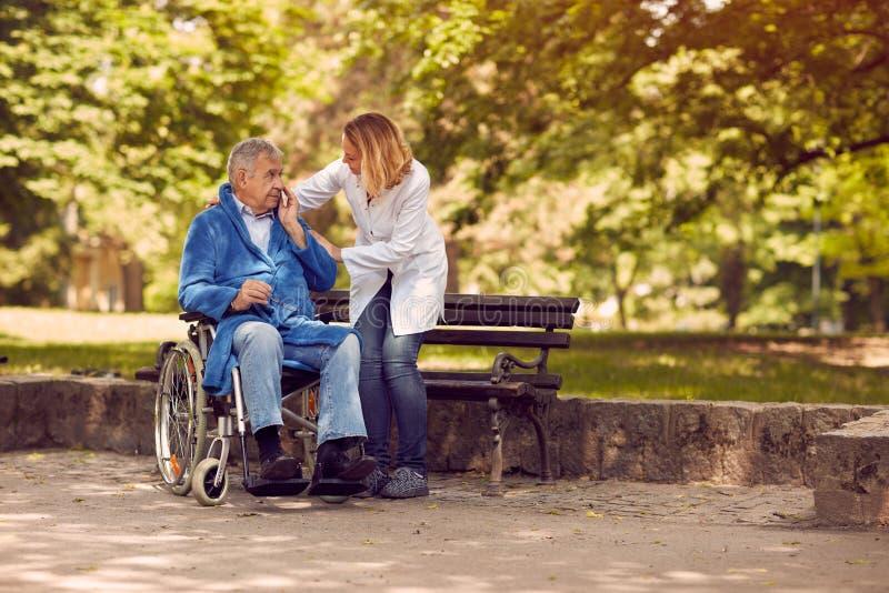 Nurse helping elderly man on wheelchair stock photo