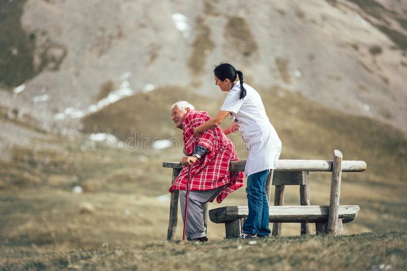 Nurse helping elderly senior man to walk on frash air. Nurse helping elderly senior men to walk on frash air outdoor royalty free stock images