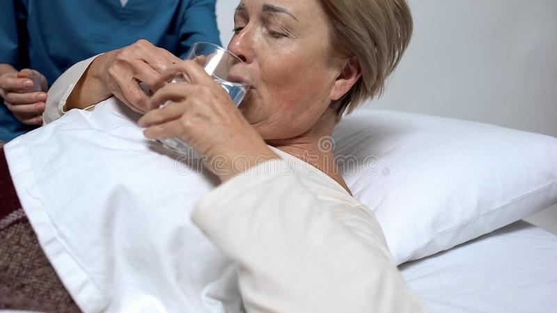 Nurse helping female patient to drink water, support and care in nursing house. Stock photo royalty free stock images