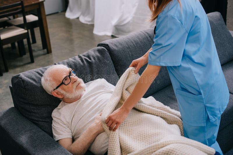Nurse helping old patient to cover stock images