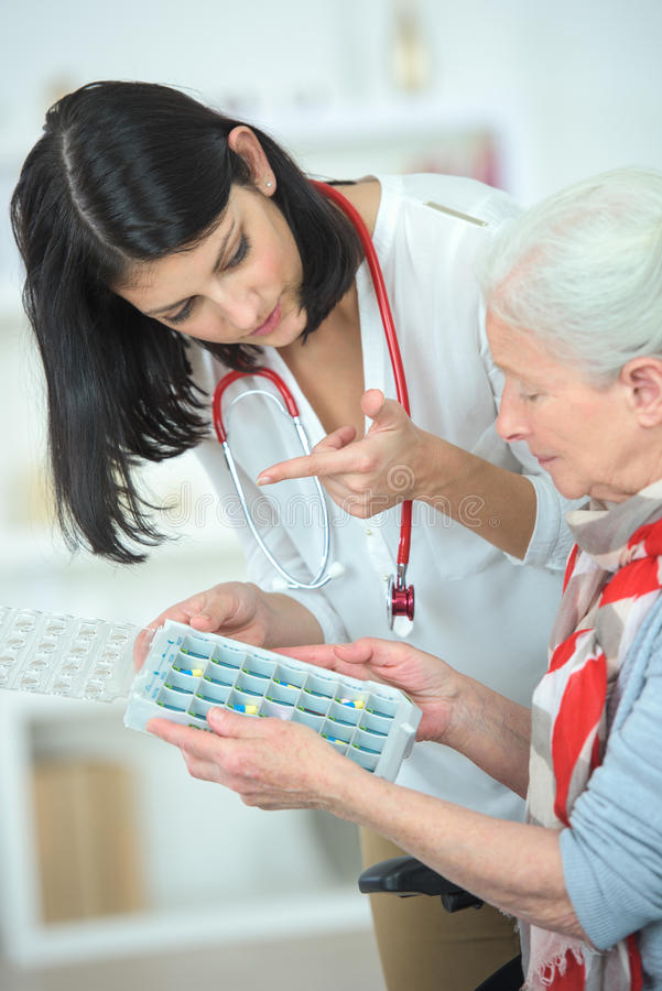 Nurse helping old woman with pill box stock images