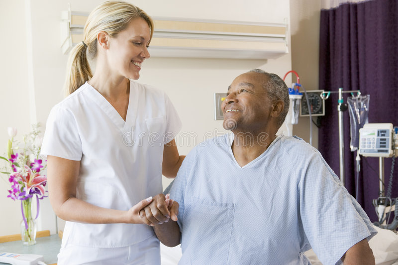 Nurse Helping Patient Sit Up In Bed stock photo