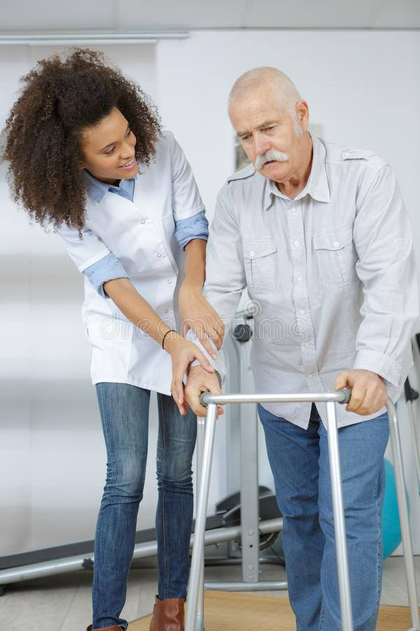 Nurse helping patient walk with frame stock photo