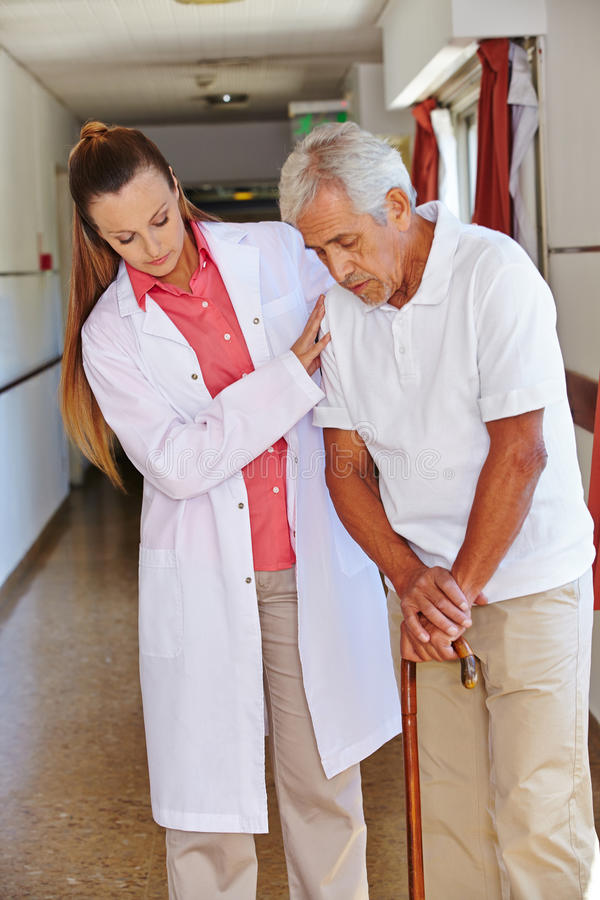 Nurse helping senior man with cane. Nurse helping senior men with cane in a nursing home royalty free stock images