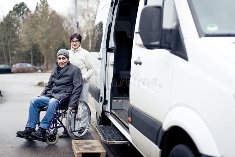 Nurse Helping Senior Man Exit A Van. Nurse helping senior men exit a van and get to his wheelchair stock photography